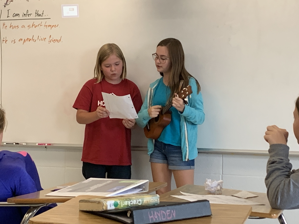 Students singing and playing a ukulele.