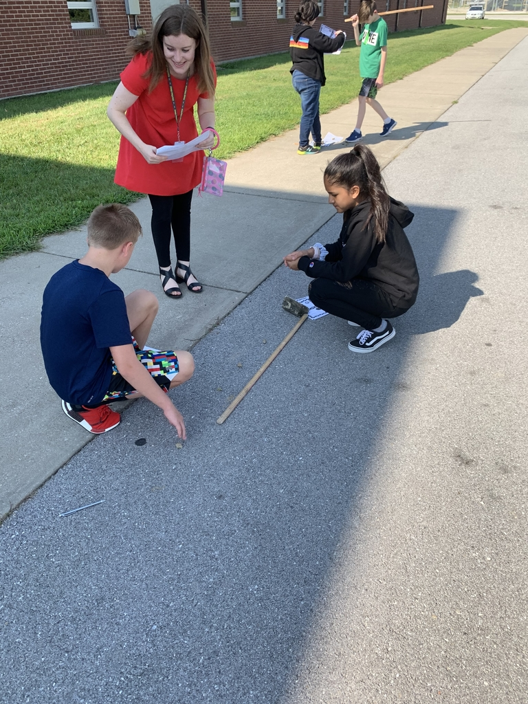 Students placing rocks on the ground to represent planets.