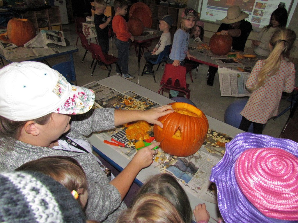 Messy hands are fun when carving pumpkins in AM preschool!